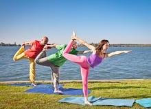 小组的人们实践在湖边的瑜伽asana。 免版税库存照片