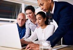 小组看同一个膝上型计算机屏幕的商务伙伴 库存图片