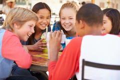 小组看在手机的CafÅ ½的孩子文本 免版税库存图片