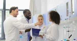 小组科学家在做笔记,混合种族队的实验室谈论实验运作在现代实验室 股票视频