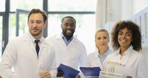 小组科学家愉快的微笑的步行在实验室在分析化学制品研究实验的试管结果以后 股票视频