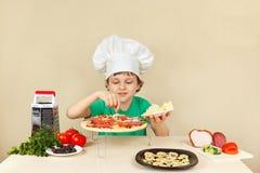 小滑稽的厨师在薄饼外壳上把一个搓碎干酪放 图库摄影