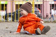 小滑稽的男孩坐地面 免版税库存照片