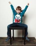 小滑稽的男孩坐椅子,手,眼睛是分类 免版税库存图片