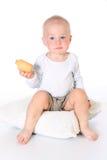小滑稽的男婴拿着并且吃曲奇饼 库存图片