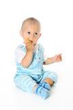 小滑稽的男婴拿着并且吃曲奇饼 免版税库存照片