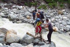小组穿过河的背包徒步旅行者游人 库存照片