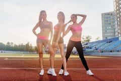 小组站立在竞技体育场和摆在的适合年轻女运动员 免版税库存照片