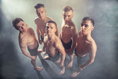 小组站起来和看照相机的舞蹈家年轻人在黑发烟性背景的演播室 库存照片