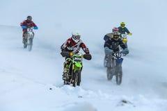小组年轻竟赛者在多雪的摩托车越野赛轨道驾驶 免版税库存照片