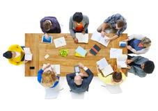 小组读笔记的Busienss人在会议桌 免版税库存照片
