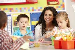 小组艺术课的基本的年龄学童与老师 库存图片