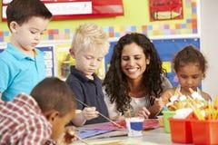 小组艺术课的基本的年龄学童与老师 免版税库存图片