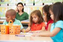 小组艺术课的基本的年龄孩子与老师 免版税库存图片
