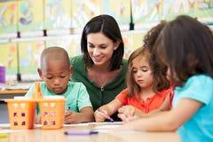 小组艺术课的基本的年龄孩子与老师 免版税库存照片