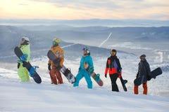 小组获得朋友的挡雪板在山上面的乐趣  图库摄影