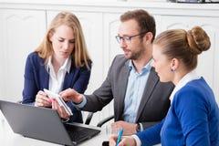 小组见面在会议桌和厕所附近的商人 免版税图库摄影