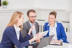 小组见面在会议桌附近的商人 免版税库存照片