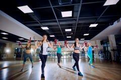 小组训练 做与一个酒吧的女孩锻炼在健身房 免版税库存照片