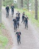 小组黑训练的妇女给在倾斜下的赛跑穿衣 免版税图库摄影