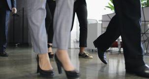 小组走在现代办公楼底视图走廊的商人,成功的商人队和 股票录像