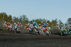 小组车手摩托车在多灰尘的轨道乘坐 库存图片