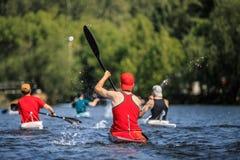 小组运动员在湖的划独木舟的人划船 库存图片