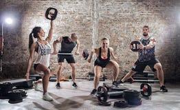 小组适合和实践与杠铃的肌肉人民 免版税库存照片