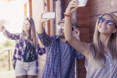 小组采取滑稽的selfie的单一文件的微笑的朋友 免版税库存照片