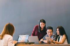 小组队偶然讨论、起始的项目业务会议或者愉快的配合突发的灵感的年轻亚裔企业同事 免版税库存图片