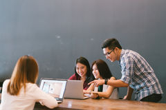 小组队偶然讨论、起始的项目业务会议或者愉快的配合突发的灵感的年轻亚裔企业同事 图库摄影
