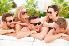 小组青年人在度假放松由游泳池的 免版税库存图片