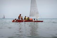 小组青年人学会驾驶有风帆的一条小船 室外海体育活动 免版税图库摄影