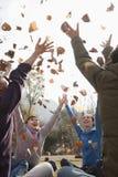 小组青年人投掷的叶子 免版税库存图片