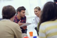 小组青年人,工作在他们的在coworking的空间的事业的起始的企业家 图库摄影
