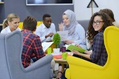 小组青年人,工作在他们的在coworking的空间的事业的起始的企业家 免版税库存图片