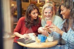 小组Cafï ¿ ½的女性朋友使用数字式设备 库存图片