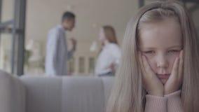 小blong哀伤的女孩的关闭在沙发坐,并且在背景非洲父亲和白种人母亲剪影  股票视频