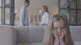 小blong哀伤的女孩的关闭在沙发坐,并且在背景非洲父亲和白种人母亲剪影  股票录像
