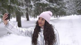 少女做selfie使用智能手机,当站立在冬天森林慢动作HD时 股票录像