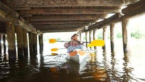 少女努力与在一艘皮船的一支桨一起使用在河 股票视频