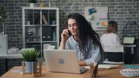 少女发表演讲关于手机在谈话办公室的屋子里接触膝上型计算机 影视素材
