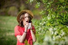 少女吹的鼻子和打喷嚏在开花的树前面的组织 影响人的季节性变态反应原 花姑娘有 免版税库存照片