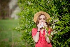 少女吹的鼻子和打喷嚏在开花的树前面的组织 影响人的季节性变态反应原 r 免版税库存照片