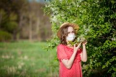 少女吹的鼻子和打喷嚏在开花的树前面的组织 影响人的季节性变态反应原 r 免版税库存图片