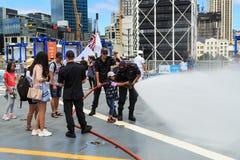 少女在两位水手帮助下拿着一条喷洒的灭火水龙带, 图库摄影