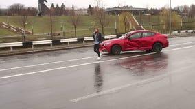 少女在她的在多雨天气的被击毁的汽车附近设置一个紧急刹车标志 影视素材