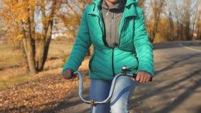 少女在秋天公园拿着弯曲的把手并且骑一辆自行车,反对 股票录像