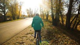 少女在路的边的骑马自行车在秋天路的 慢的行动 影视素材
