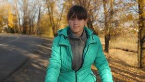 少女在路的骑马自行车在以黄色树为背景的秋天公园 影视素材